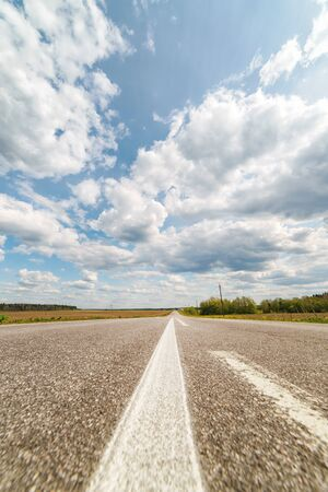 Endless country road to the horizon under cloudy sky. First person view