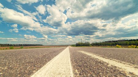 Endless country road to the horizon under cloudy sky. Low point of view cinematic panoramic view