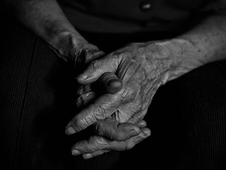 Elderly woman folded her hands on her knees. Low key black and white image 版權商用圖片