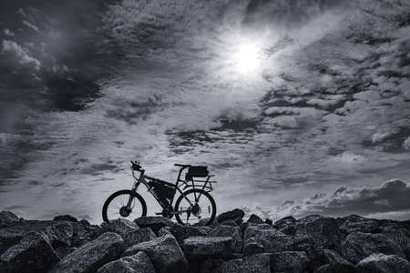 Lone electric bike against dramatic sky. Black and white image