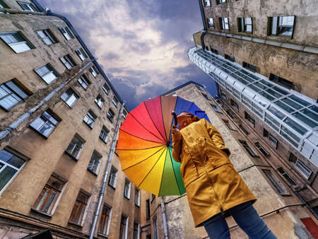 A woman in a bright yellow raincoat with a rainbow umbrella standing in an old courtyard well and looking at the dark stormy sky. Saint Petersburg, Russia