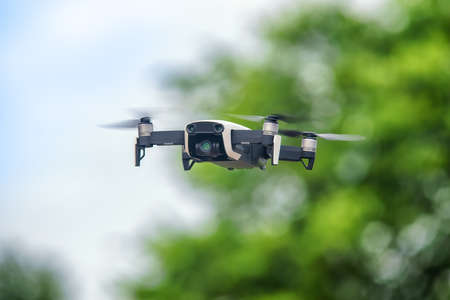 Small drone in flight against defocused foliage. Selective focus on the drone