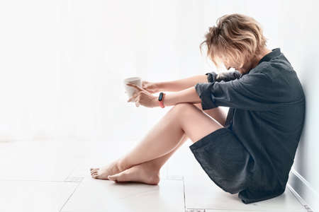 Barefoot woman sitting on the floor in clear light room with coffee cup in the hands. Morning and relaxation theme high key image Stok Fotoğraf