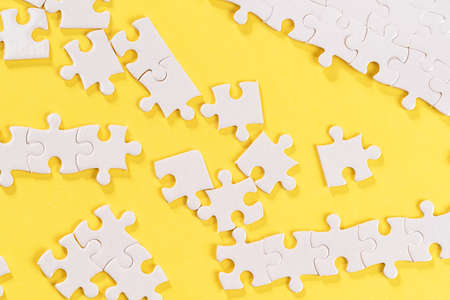 Disassembled white jigsaw puzzle pieces on yellow background.