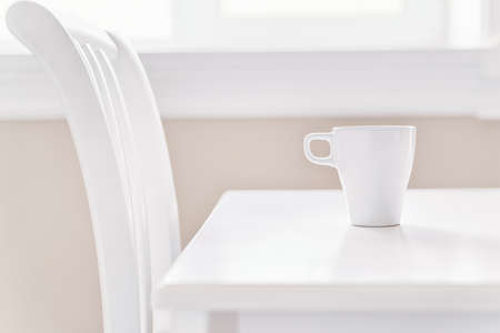 White coffee cup on the clear white table side view. Selective focus on the cup, high key Stok Fotoğraf