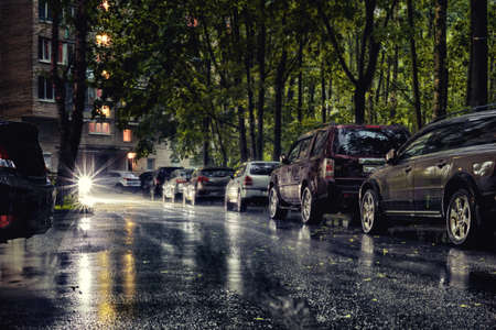 Generic city courtyard with parked cars under heavy rain. HDR street photo