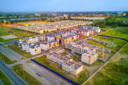Small residential area of three floors houses ready and under construction. Aerial view with tilt-shift effect
