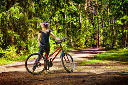 Woman in wreath of daisies with bike alone in the bright green forest. Outdoors summer sport and recreation theme portrait