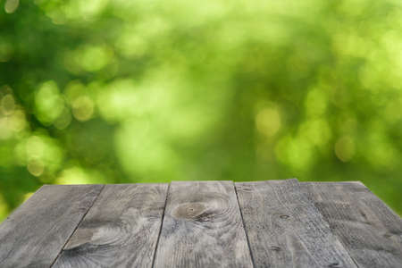 Black wooden table template with defocused foliage as background Selective focus on the table Stok Fotoğraf