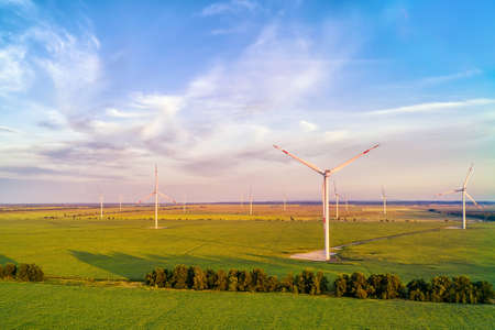 Wind power plant in the green field against cloudy sky at sunset. Panoramic aerial view