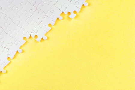 White jigsaw puzzle pieces on yellow. Abstract background with copy space Stok Fotoğraf