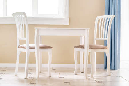 Two white chairs and white empty table by the window in a clean large room. Interior image with no people