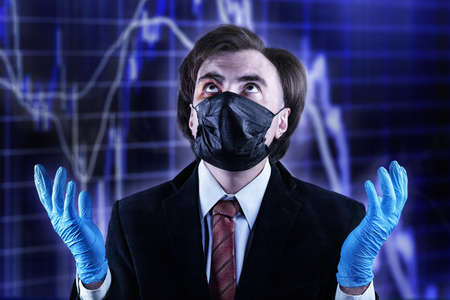 Businessman with a bruise on his face in an official suit, medical mask and gloves, raising his eyes to heaven against the blurred stock chart. Crisis, epidemic, bad luck and accident theme