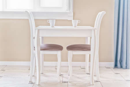 Table, two chairs and two cups of coffee in a bright, clear room. High key image, natural light. Stok Fotoğraf