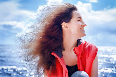 Smiling woman in a red sleeveless jacket sitting by the sea with long curly hair flying in the wind. Outdors profile portrait