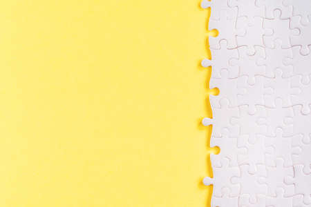 White jigsaw puzzle pieces on yellow. Abstract template and background with copy space