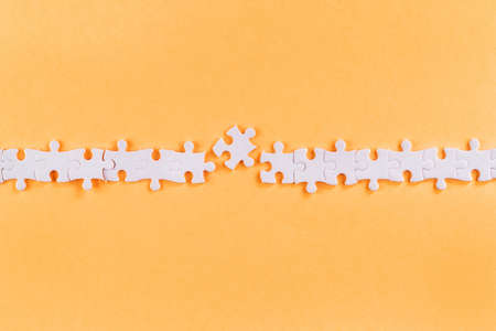 Disrupted row of white jigsaw puzzle pieces with missing link on orange background