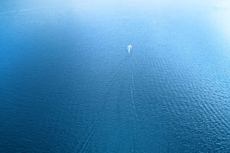 Lonely motor boat on the empty high seas. High angle aerial view
