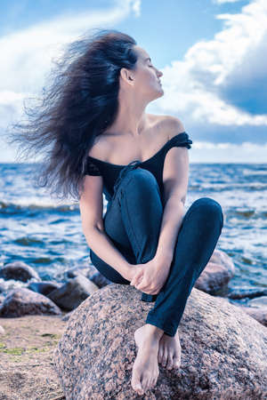 Calm brunette woman sitting on a stone by the sea with long hair flying in the wind. Blue tinted outdors portrait