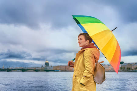 Girl in yellow raincoat with rainbow colored umbrella standing on the embankment against overcast sky. Saint Petersburg, Russia