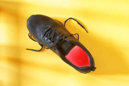 Single black boot with red illumination inside on yellow background top view. Abstract walking and footwear theme image