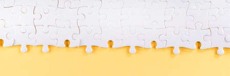 Assembled white jigsaw puzzle pieces on yellow. Long panoramic texture and background
