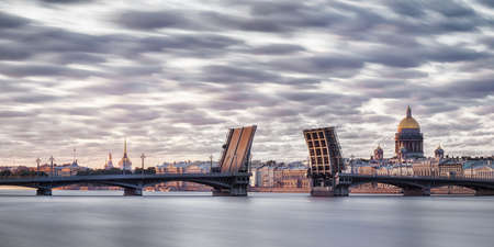 Neva river in Saint Petersburg panoramic view with divorced Blagoveshchenskiy bridge, st. Isaak cathedral and Admiralty at white nights. Long exposure