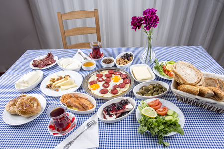 Traditional Turkish Breakfast with eggs, pasta, salad, borek, grapes, turkish eggs, menemen, bread, olives and cheese