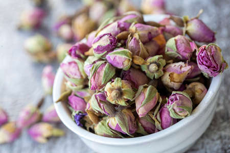 Dried pink roses on the wooden background. Dried pink roses herbal tea. 免版税图像