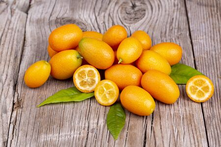 Top view of bunch of fresh kumquats in the organic food market. Some kumquats is cutted.