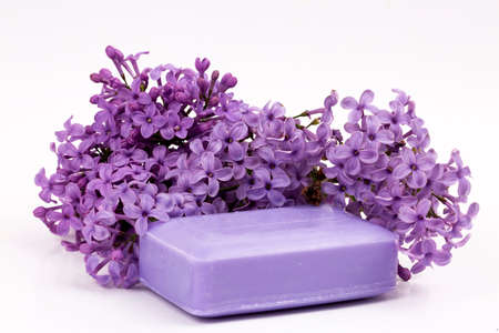 Natural handmade soap and lilac flowers on white background
