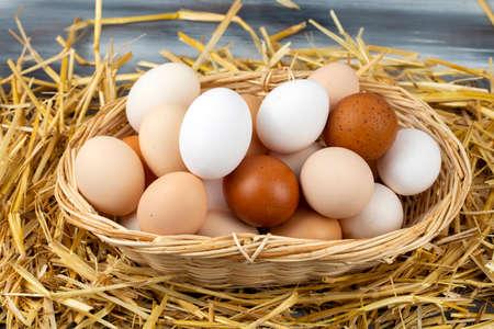 Raw eggs in dry straw. Food concept photo. Фото со стока