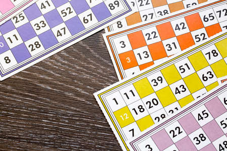 Colorful bingo game cards and numbers on white background, close up, isolated.