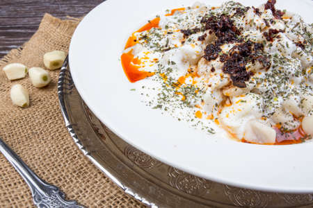 Plates of traditional Turkish food. Manti with tomato sauce