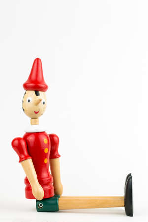 Wooden Pinocchio doll sitting isolated on white background.