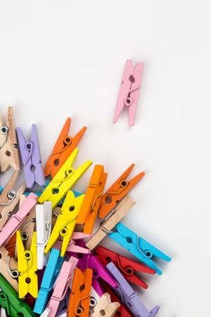 Multicolored wooden clothes pegs on a white background.