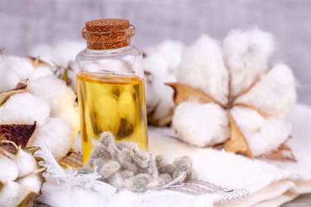 Cottonseed oil in a glass bottle on a wooden surface.