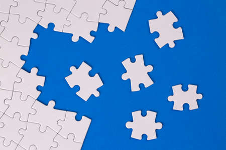 Missing jigsaw puzzle pieces. Business concept. Fragment of a folded white jigsaw puzzle and a pile of uncombed puzzle elements against