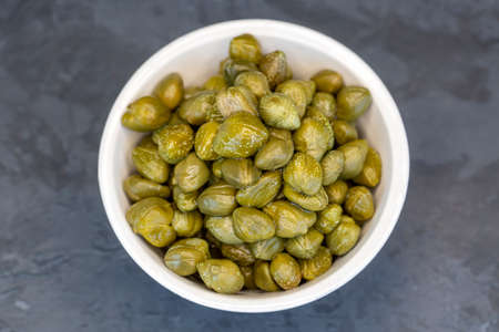 Pickled capers in a glass bowl on a dark background, top view close up (Turkish name; capers) 免版税图像
