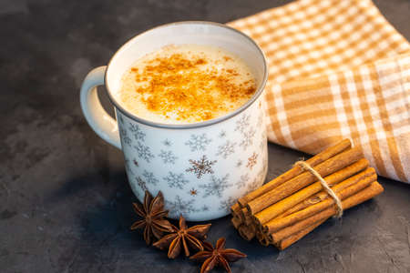 Close up white cup of salep milky hot drink of Turkey with cinnamon powder healthy spice on black wooden background (Sahlep - salep) 免版税图像