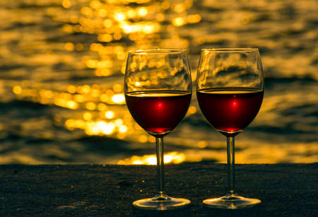 Pair of red wine glasses on the beach.