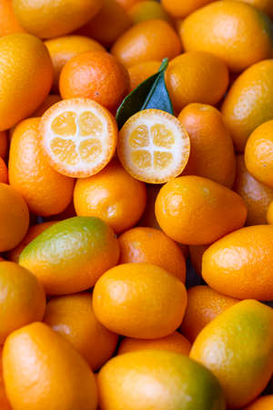 Top view of bunch of fresh kumquats in the organic food market. Some kumquats is cutted 免版税图像