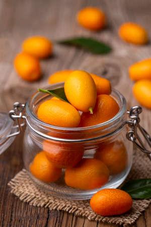 Kumquat or cumquat on wooden table 免版税图像