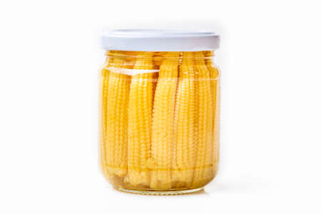 Pickled young baby corn cobs in jar isolated on white background.