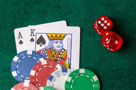 Playing cards, dice and poker chips from above on the green poker table