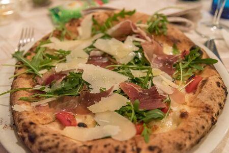 Delicious pizza with parma ham, grana padano and rucola