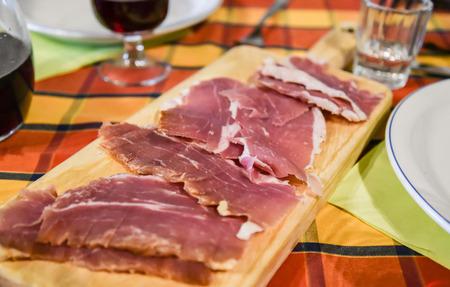 gressins: Salaisons servis sur une planche de bois dans un agriturismo en Basilicate, Italie