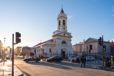 Unidentified people walk at the central square of Punta Arenas, Chile