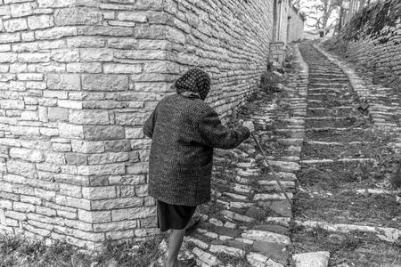 An elderly woman walking the streets of Vitsa in Zagori area, Northern Greece