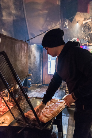 Man grilling salmon on a fire in a traditional hut near Rovaniemi in Lapland, Finland